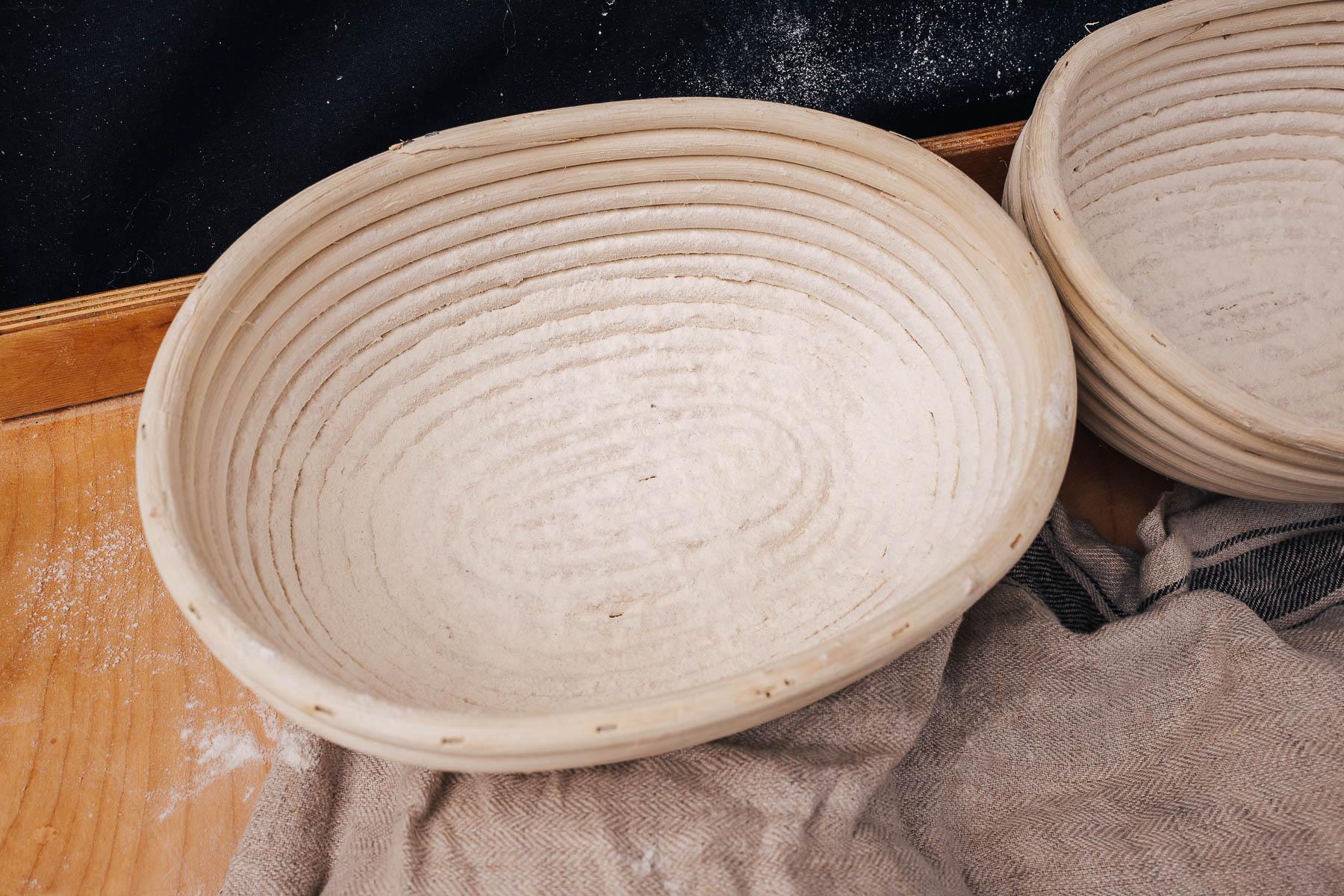 Przygotuj koszyki do wyrastania podsypując je dokładnie mąką. Ten krok zapobiegnie przyklejaniu się ciasta do koszyka.