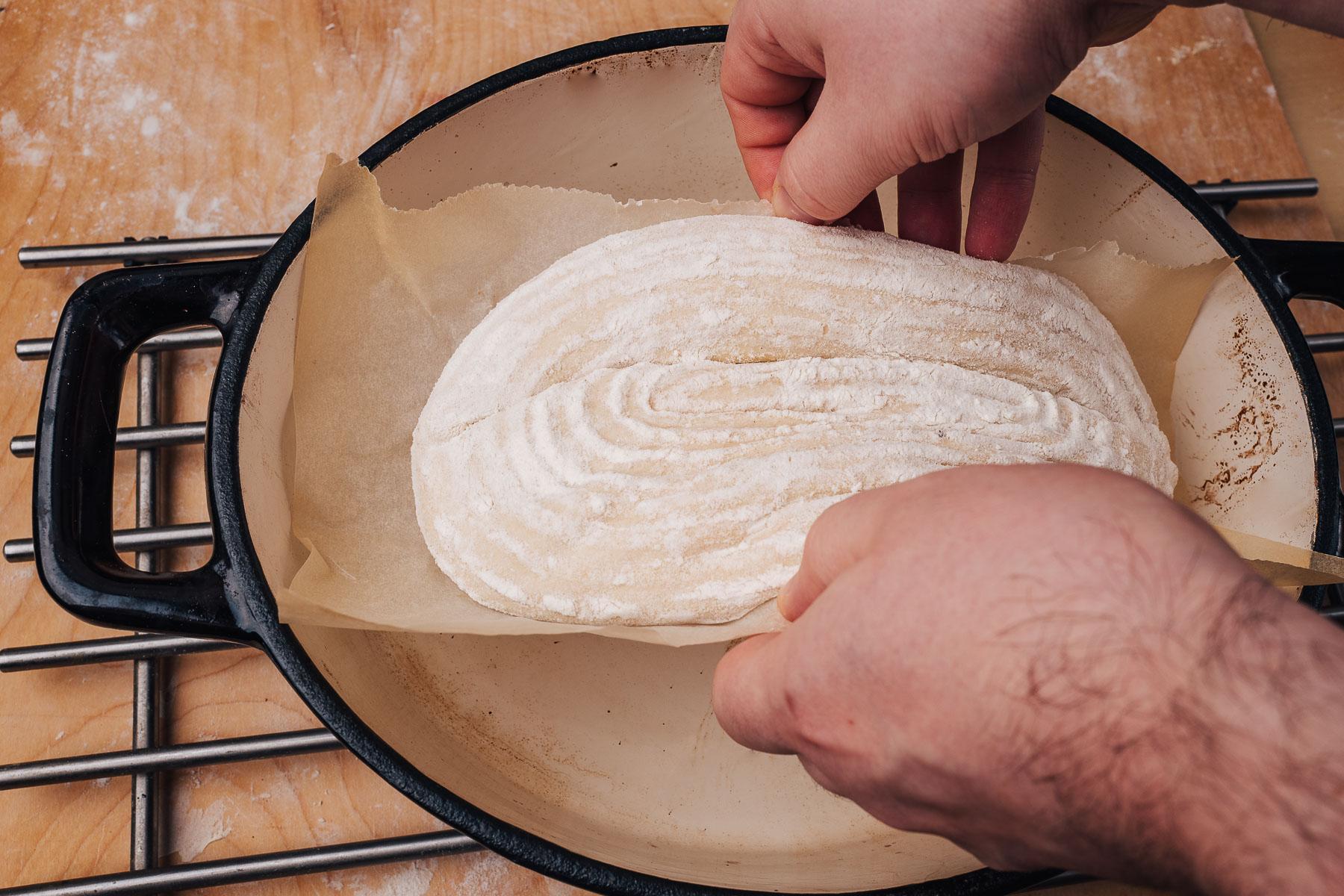 Ostrożnie przełóż ciasto do garnka żeliwnego i zakryj je przykrywką. Następnie włóż do piekarnika.